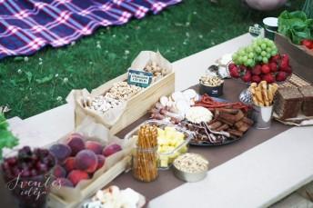 Karinis teminis piknikas gamtoje, lauke, užkandžių iir desertų stalas