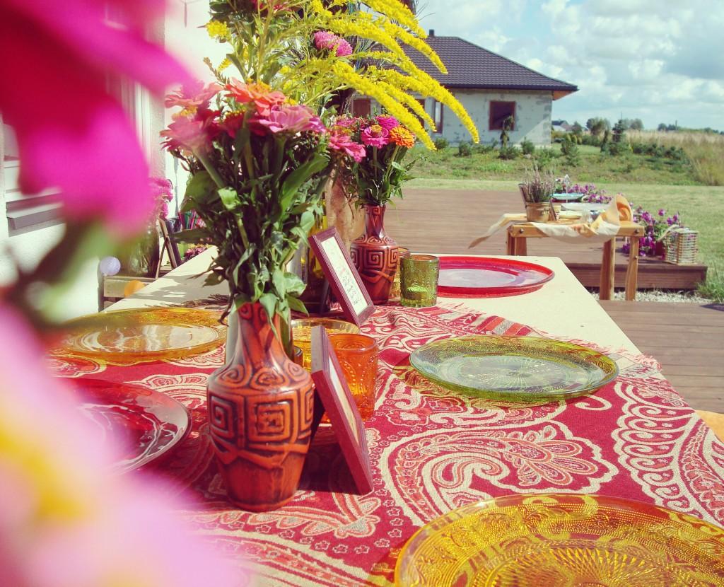 Spalvotos lėkštės ir marga staltiesė, ryškus šventės dekoras